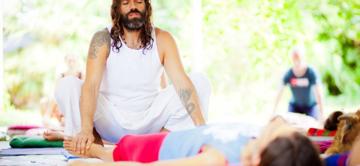 A man medicates as others practice yoga