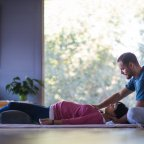 One person helps another in this yoga exercise