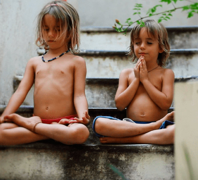 Two siblings meditate side by side