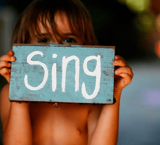 """A child holding a sign that says """"sing"""""""
