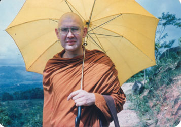 A monk keeps shade from the sun with an umbrella